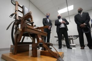 Standing around an electric chair